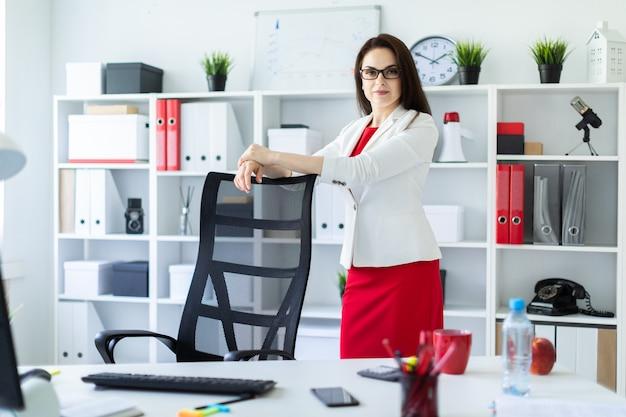 Une jeune fille se tient dans le bureau près d'une chaise à haut dossier.