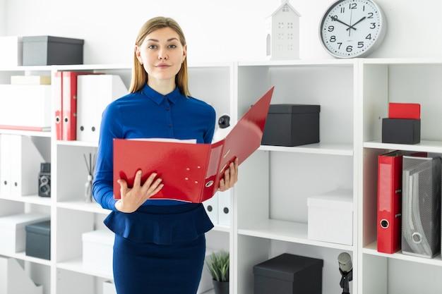 Une jeune fille se tient dans le bureau près du refuge et tient un dossier avec des documents dans ses mains.