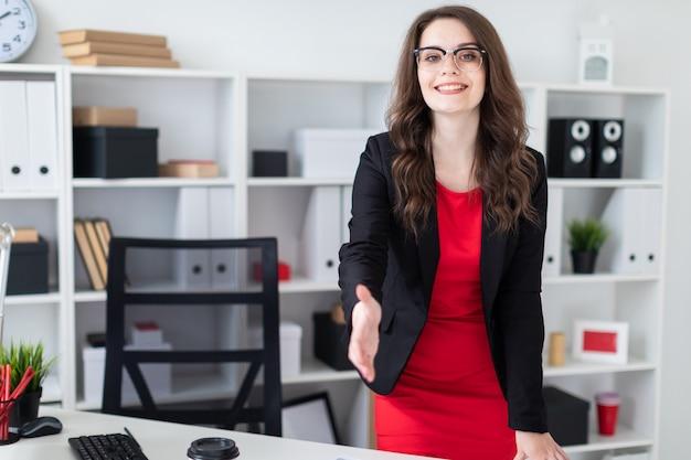 Une jeune fille se tient dans le bureau près de la table et tend la main en avant