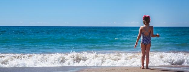 La jeune fille se tient dos à la plage sur fond d'une belle vague