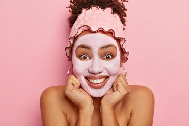 Jeune fille se tient avec un masque de rajeunissement de boue, tient les mains sous le menton, regarde joyeusement, se tient avec les épaules nues, a un teint bien soigné, des soins de beauté réguliers