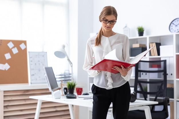 Une jeune fille se tient près d'un bureau d'ordinateur et fait défiler un dossier contenant des documents.