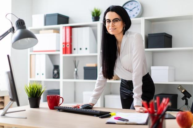 Une jeune fille se tient près d'un bureau d'ordinateur, lui imposant les mains.