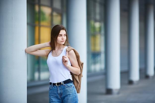 Jeune fille se tient près du bâtiment. espace de copie.