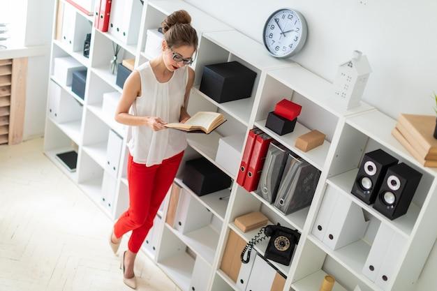 Une jeune fille se tient près de l'étagère et tient un livre ouvert dans ses mains.
