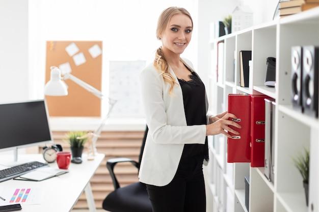Une jeune fille se tient près d'un rack dans le bureau et sort un dossier.