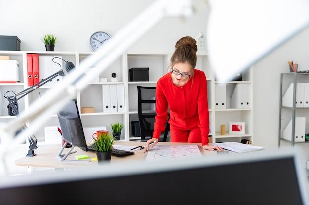 Une jeune fille se tient près d'une table dans son bureau, tient un marqueur dans sa main et regarde le tableau magnétique.