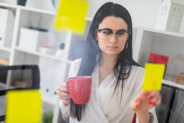 Une jeune fille se tient près d'un tableau avec des autocollants et tient une tasse rouge dans ses mains.