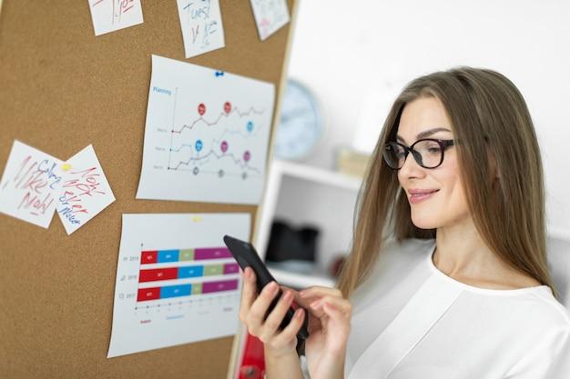 Une jeune fille se tient près d'un tableau avec des autocollants et tient un téléphone dans ses mains.
