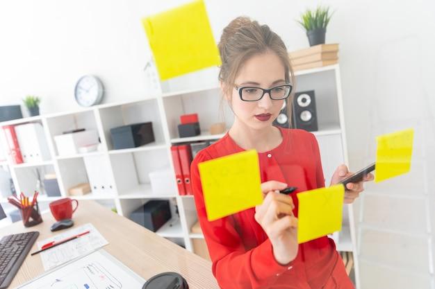 Une jeune fille se tient près d'un tableau transparent avec des autocollants et est titulaire d'un marqueur et d'un téléphone.