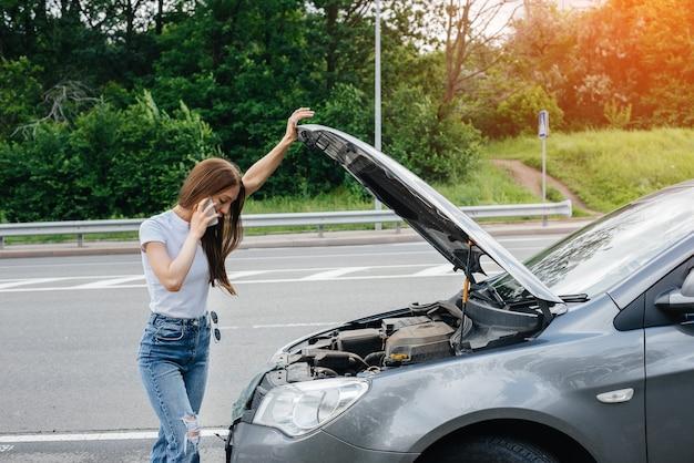 Une jeune fille se tient près d'une voiture en panne au milieu de l'autoroute et appelle à l'aide au téléphone