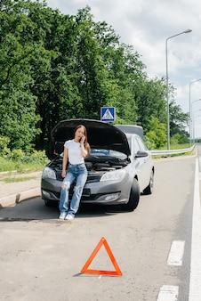 Une jeune fille se tient près d'une voiture en panne au milieu de l'autoroute et appelle à l'aide par téléphone. panne et panne de la voiture. en attente d'aide.
