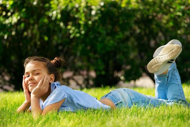 Une jeune fille se trouve dans un pré avec ses mains soutenant sa tête. enfance en été dans le parc. photo de haute qualité