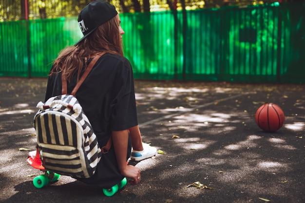 Jeune fille, séance, sur, plastique, orange, penny, shortboard, sur, asphalte, dans, casquette