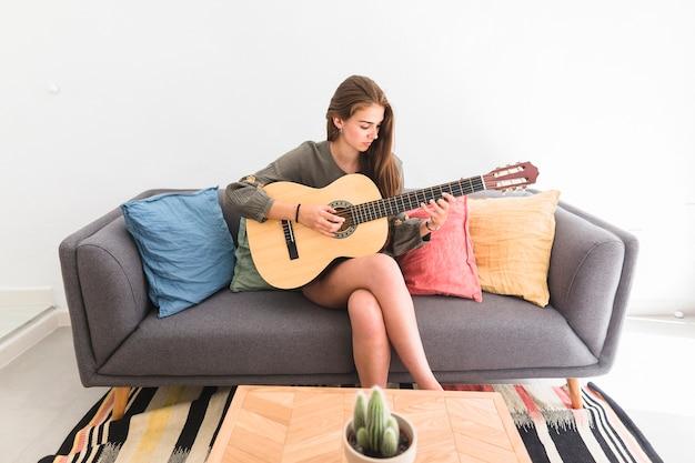 Jeune fille, séance, sofa, jouer guitare