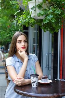 Jeune fille séduisante aux cheveux longs, boire du café avec un muffin dans un café en plein air