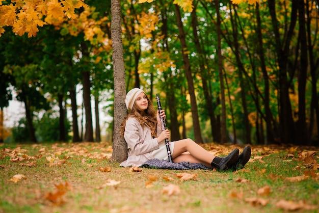 Jeune fille séduisante avec clarinette, ébène en automne parc
