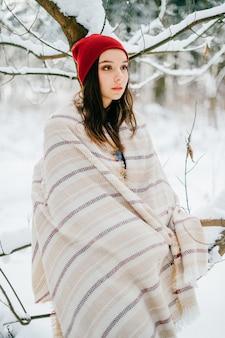 Jeune fille séduisante couvrant avec une cape chaude posant parmi les branches de neige dans la forêt