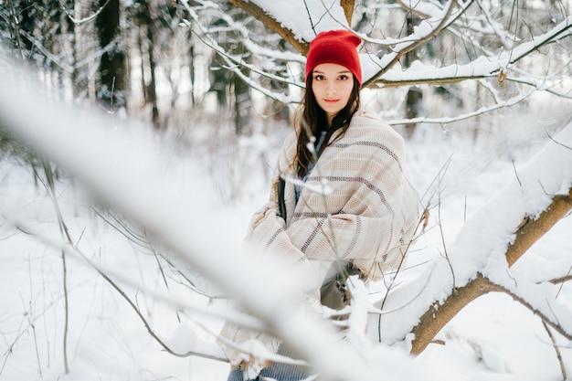 Jeune fille séduisante couvrant avec une cape chaude posant parmi les branches de neige