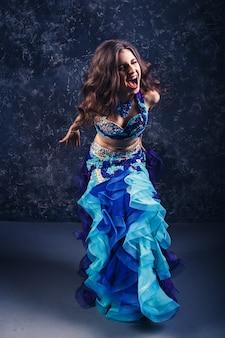 Jeune fille séduisante dans un costume bleu danse danse du ventre.