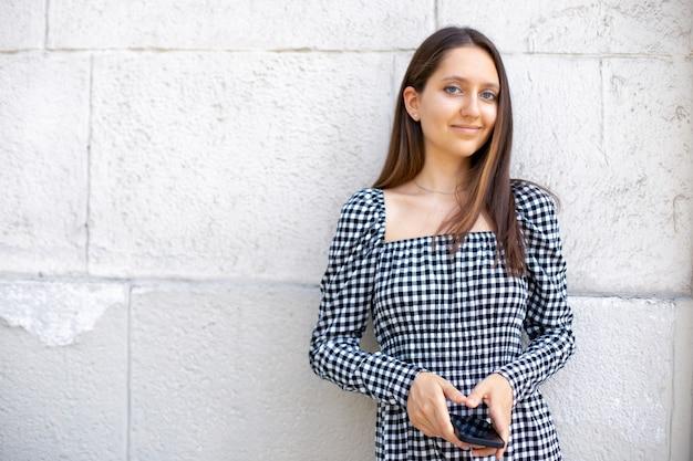 Jeune fille séduisante dans une robe à carreaux tenant un téléphone dans ses mains en regardant la caméra sur un fond de mur blanc isolé