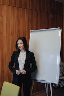 Jeune fille séduisante émotionnelle dans des vêtements de style d'affaires travaillant avec paperboard