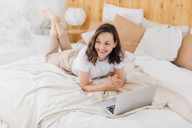 Une jeune fille séduisante est allongée dans son lit et vérifie l'appartement lumineux moderne des réseaux sociaux
