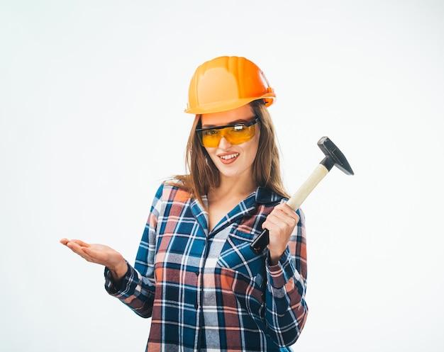 Jeune fille séduisante heureuse dans la construction d'un casque orange et de lunettes avec un marteau. photo de studio isolée complète d'une artisane émotionnelle.