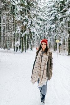 Jeune fille séduisante hipster marchant dans la forêt de neige