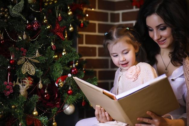 Jeune fille séduisante portant un pyjama chaud et un couvre-lit près de l'arbre du nouvel an. ambiance de noël.