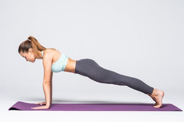 Jeune fille séduisante pratiquant le yoga isolé. concept de vie saine et équilibre naturel entre le corps et le développement mental. toute la longueur