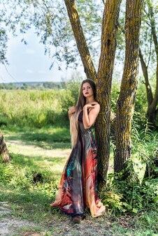 Jeune fille séduisante en robe d'été posant en plein air