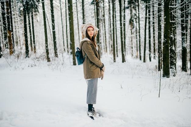Jeune fille séduisante avec un turban de l'écharpe posant dans la forêt de neige