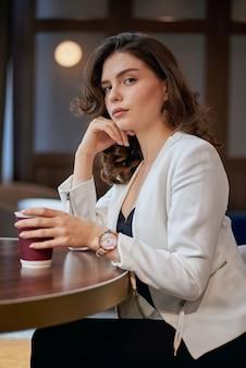 Jeune fille sérieuse, buvant du café dans un café