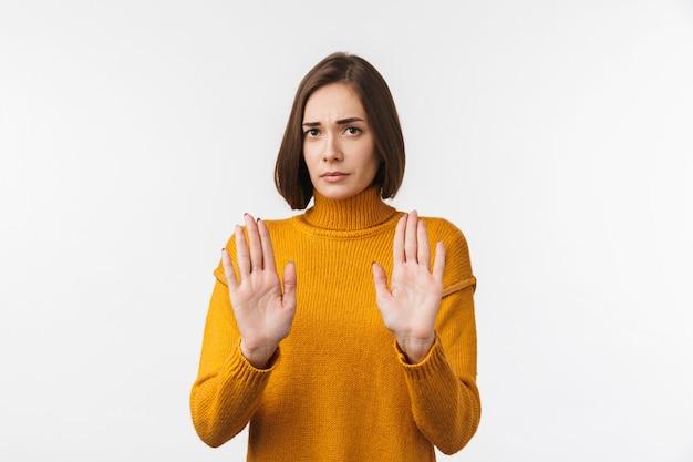 Jeune fille sérieuse debout isolée sur un mur blanc, montrant un geste d'arrêt