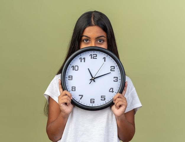 Jeune fille sérieuse en t-shirt blanc tenant une horloge murale cachant son visage derrière elle