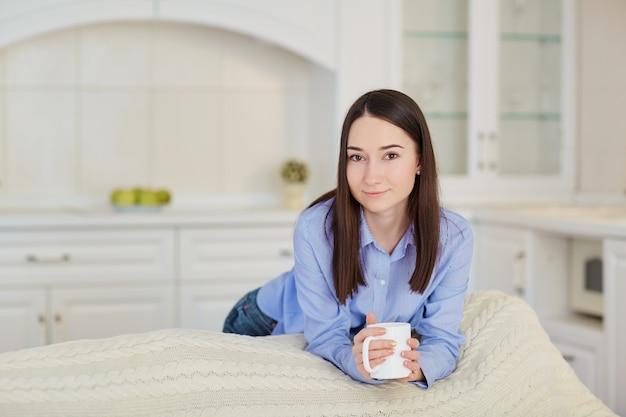 Jeune fille sérieuse avec une tasse de boisson chaude dans la cuisine.