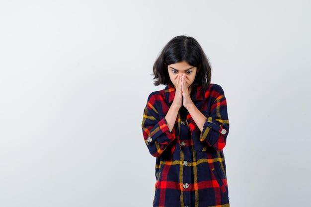 Jeune fille serrant les mains en position de prière en chemise à carreaux et l'air concentré. vue de face.