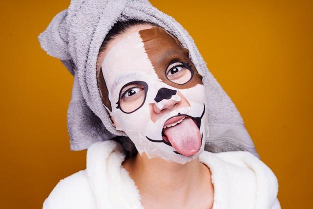 Jeune fille avec une serviette sur la tête, sur son visage un masque avec une photo d'un museau de chien, montre une langue