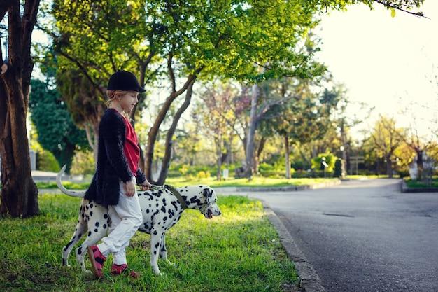 Jeune fille avec ses chiens dalmates dans un parc printanier. heure du coucher du soleil, rouge, blanc et noir