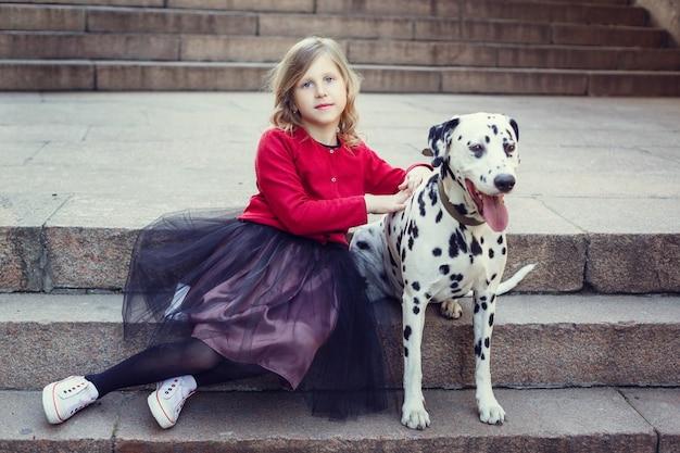 Jeune fille avec ses chiens dalmates dans un parc printanier.