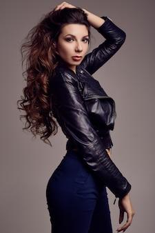 Jeune fille sexy aux cheveux longs en veste de cuir