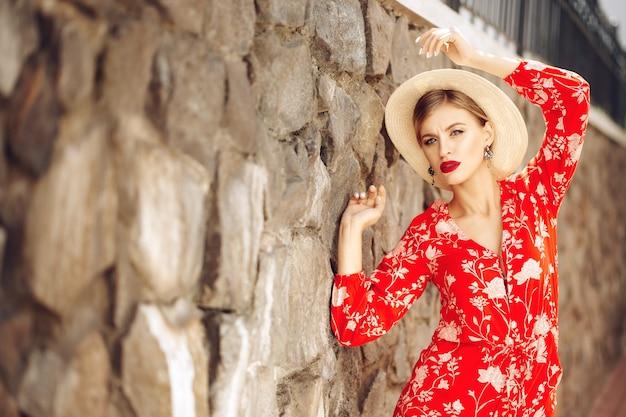 Jeune fille sexy belle à la mode dans un costume rouge et un chapeau se tient près d'un mur de briques