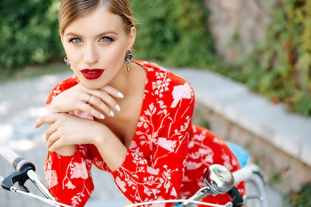 Jeune fille sexy belle à la mode dans un costume rouge en été dans une ville à vélo