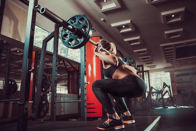 Jeune fille sexy dans la salle de sport faisant squat
