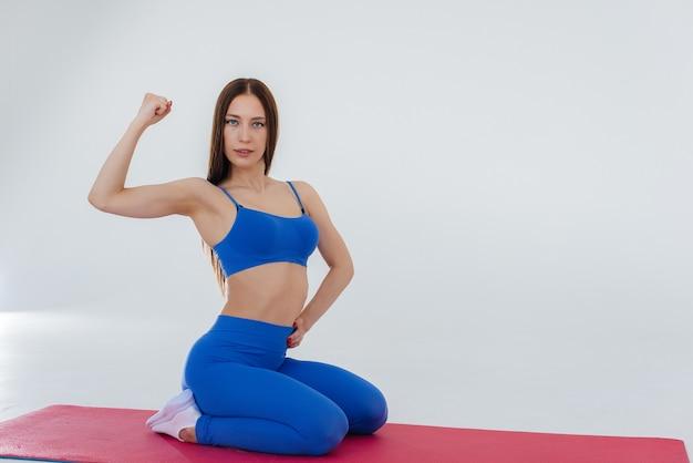 Une jeune fille sexy effectue des exercices de sport sur un mur blanc