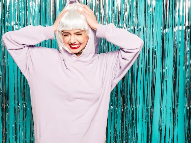 Jeune fille sexy hipster souriante en perruque blanche et lèvres rouges. belle femme à la mode dans les vêtements d'été. devenir fou