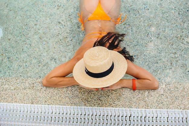 Une jeune fille sexy à lunettes et un chapeau sourit joyeusement dans le contexte d'un grand parc aquatique moderne par une journée ensoleillée. bonnes vacances vacances. vacances d'été et tourisme.