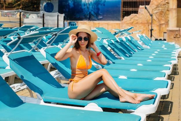 Une jeune fille sexy à lunettes et un chapeau sourit joyeusement et prend un bain de soleil sur une chaise longue par une journée ensoleillée. bonnes vacances vacances. vacances d'été et tourisme.