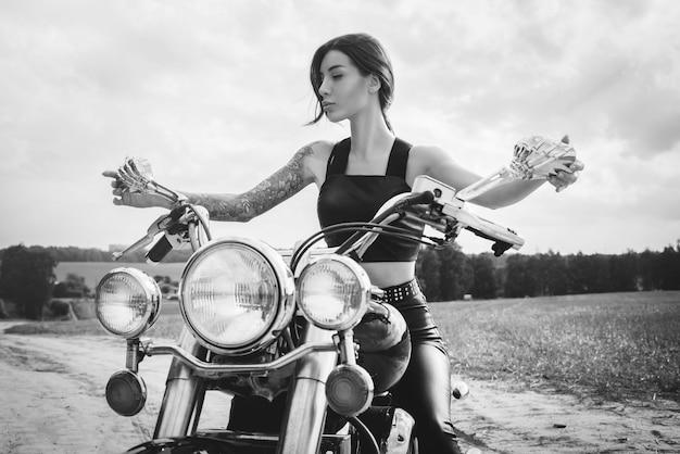 Jeune fille sexy posant sur une moto au coucher du soleil. concept de sport automobile. technique mixte